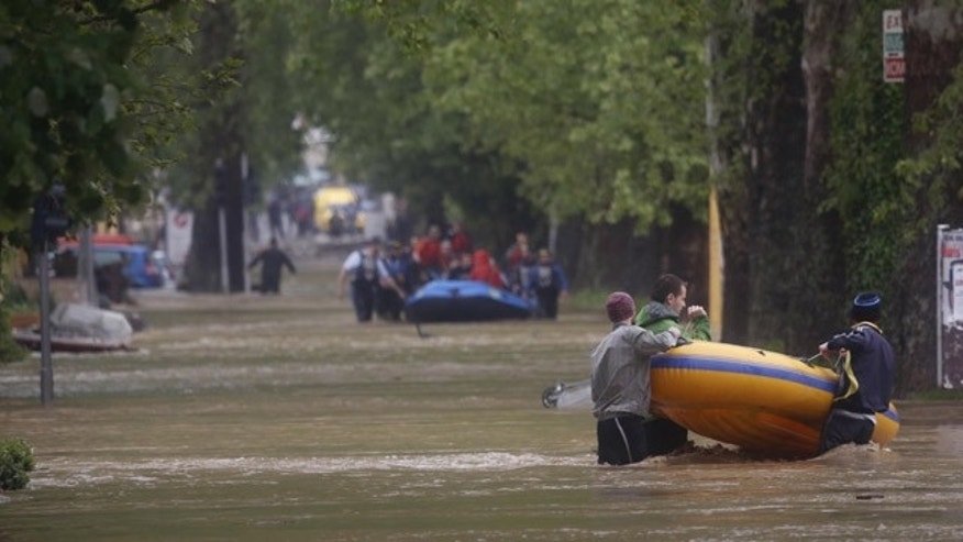 May 16, 2014: Bosnian volunteers carry an inflatable boat as they distribute food supplies to people stranded due to floods in the town of Maglaj, 150 kms north of Sarajevo, Friday May 16, 2014. (AP Photo/Amel Emric)