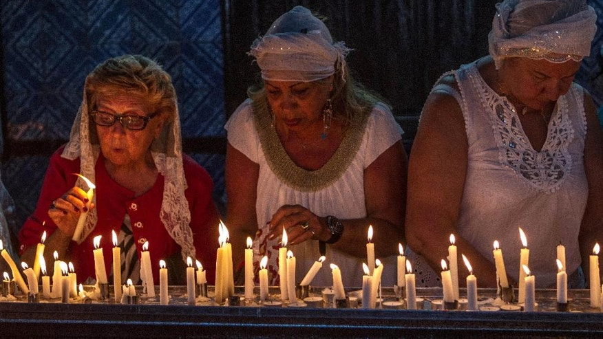 Jewish pilgrims light candles in the Ghriba synagogue, the oldest Jewish monument built in Africa more than 2,500 years ago, as they  attend the annual Jewish pilgrimage in the resort of Djerba, Tunisia, Friday April 26, 2013. Jews coming from Tunisia, Europe or Israel make their annual pilgrimage to El Ghriba synagogue, commemorating the death of Shimon Bar Yohai, a second-century kabbalistic rabbi who authored a famous religious text known as The Zohar. (AP Photo/Aimen Zine)