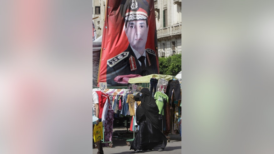 Egyptians walk past a portrait of Egyptian Presidential hopeful, retired Field Marshal Abdel-Fattah el-Sissi, at a market in Cairo, Egypt, Saturday, May 17, 2014. El-Sissi faces leftist Hamdeen Sabahi, who has the support of youth groups who led the 2011 uprising against autocrat Hosni Mubarak. El-Sissi, who led the July 3, 2013 overthrow after millions protested against Islamist President Mohammed Morsi, is widely expected to win the May 26-27 vote on a wave of nationalistic, anti-Islamist fervor. (AP Photo/Amr Nabil)