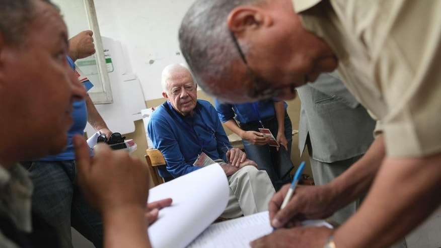 FILE -- In this Wednesday, May 23, 2012 file photo, former U.S. President Jimmy Carter, center, observes the election process inside a polling station in the Sayeda Aisha neighborhood of Cairo, Egypt. Carter is warning Egypt that its transition to democracy after years of political turmoil is faltering ahead of presidential elections planned for later this month, in a statement Friday, May 16, 2014. His Carter Center won't be sending observers for Egypt's May 26-27 election, which many believe retired Field Marshal Abdel-Fattah el-Sissi handily will win following the overthrow of Islamist President Mohammed Morsi last year that he led. (AP Photo/Thomas Hartwell, File )