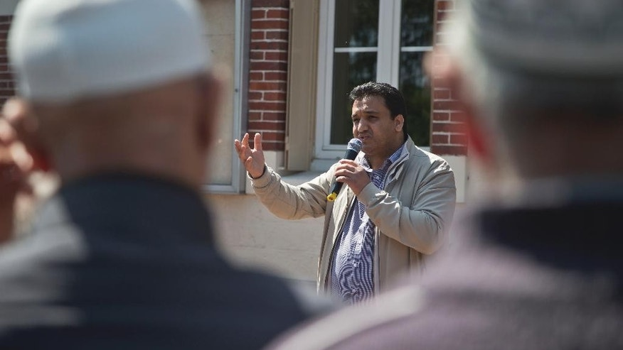 Leader of the Muslim association of Mantes la Ville Abdelaziz El Jaouari, gestures as he speaks to the demonstrators  outside the town hall in Mantes la Ville, north west of Paris, Friday, May 16, 2014, which are gathering in protest of the ban of a new mosque. A new mosque for Muslims approved last year and paid with a heavy deposit is suddenly in limbo in a town outside Paris, and new shops in a southern town that reflect Muslims' traditions will be banned. Newly-installed far-right mayors in Mantes-la-Ville, west of the French capital, and in Beaucaire, in southwest France, are rolling out their programs and the large Muslim populations in their towns risk getting crushed. (AP Photo/Michel Euler)