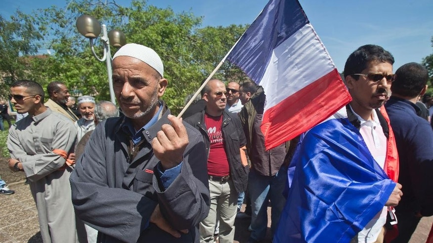Demonstrators with French flags gather outside the town hall in Mantes la Ville, north west of Paris, Friday, May 16, 2014, in protest of the ban of a new mosque. A new mosque for Muslims approved last year and paid with a heavy deposit is suddenly in limbo in a town outside Paris, and new shops in a southern town that reflect Muslims' traditions will be banned. Newly-installed far-right mayors in Mantes-la-Ville, west of the French capital, and in Beaucaire, in southwest France, are rolling out their programs and the large Muslim populations in their towns risk getting crushed. (AP Photo/Michel Euler)