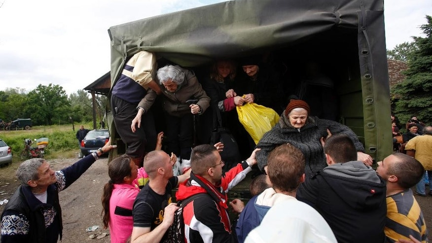 People help old women out of a military truck during evacuation from Obrenovac, some 30 kilometers (18 miles) southwest of Belgrade Serbia, Saturday, May 17, 2014. Record flooding in the Balkans leaves at least 20 people dead in Serbia and Bosnia and is forcing tens of thousands to flee their homes. Meteorologists say the flooding is the worst since records began 120 years ago. (AP Photo/Darko Vojinovic)