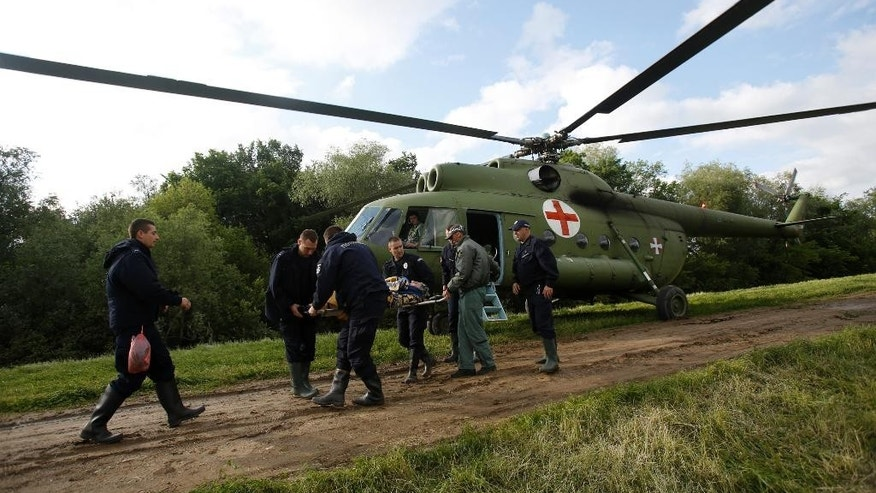 Serbian police officers carry an old woman from a military helicopter during evacuation from Obrenovac, some 30 kilometers (18 miles) southwest of Belgrade Serbia, Saturday, May 17, 2014. Record flooding in the Balkans leaves at least 20 people dead in Serbia and Bosnia and is forcing tens of thousands to flee their homes. Meteorologists say the flooding is the worst since records began 120 years ago. (AP Photo/Darko Vojinovic)
