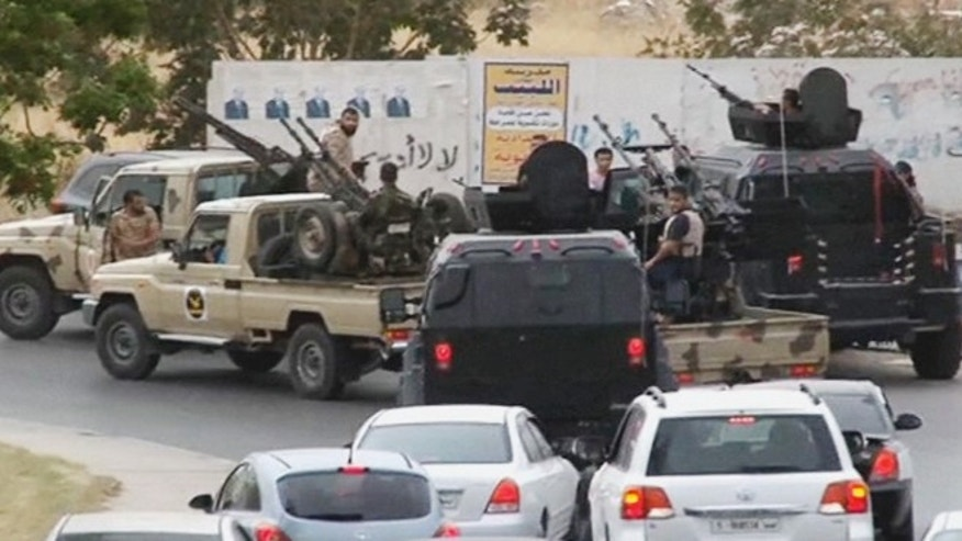 May 18, 2014: In this image made from video provided by the Libyan national army via AP Television, vehicles with heavy artillery of the Tripoli joint security forces move closer to the parliament building after troops of Gen. Khalifa Hifter targeted Islamist lawmakers and officials at the parliament in Tripoli, Libya. Forces loyal to a rogue Libyan general attacked the country's parliament Sunday, expanding his eastern offensive against Islamists into the heart of the country's capital.