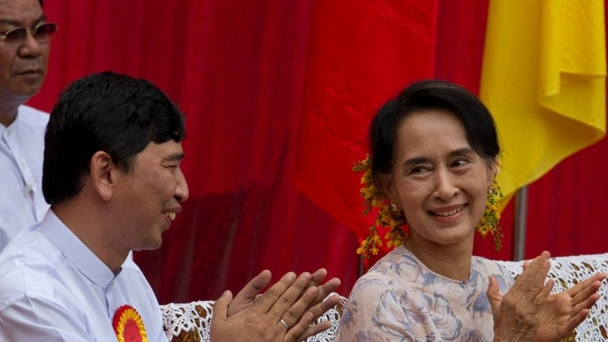 Myanmar opposition leader Aung San Suu Kyi, right, and pro-democracy activist Min Ko Naing clap hands during a public rally in Yangon, Myanmar, Saturday, May 17, 2014. Democracy activists joined Suu Kyi for the first time calling for an amendment to Myanmar's constitution, a move she says is necessary if next year's general elections are to be free and fair. (AP Photo/Gemunu Amarasinghe)