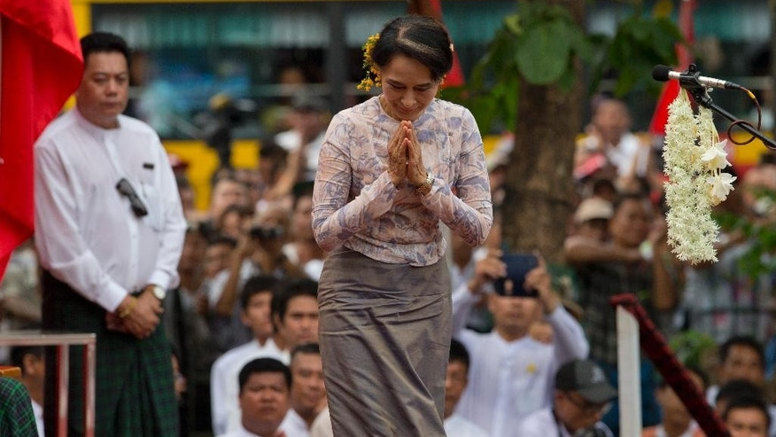 Myanmar opposition leader Aung San Suu Kyi greets Buddhist monks during a public rally in Yangon, Myanmar, Saturday, May 17, 2014. Democracy activists joined Suu Kyi for the first time calling for an amendment to Myanmar's constitution, a move she says is necessary if next year's general elections are to be free and fair.(AP Photo/Gemunu Amarasinghe)