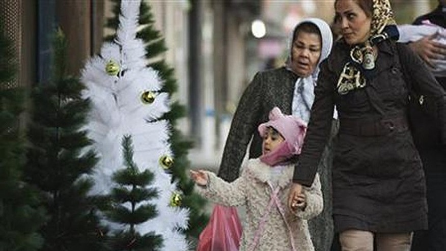 Girl looks at Christmas tree as she and her mother walk past Christmas decorations in central Tehran. (Reuters)