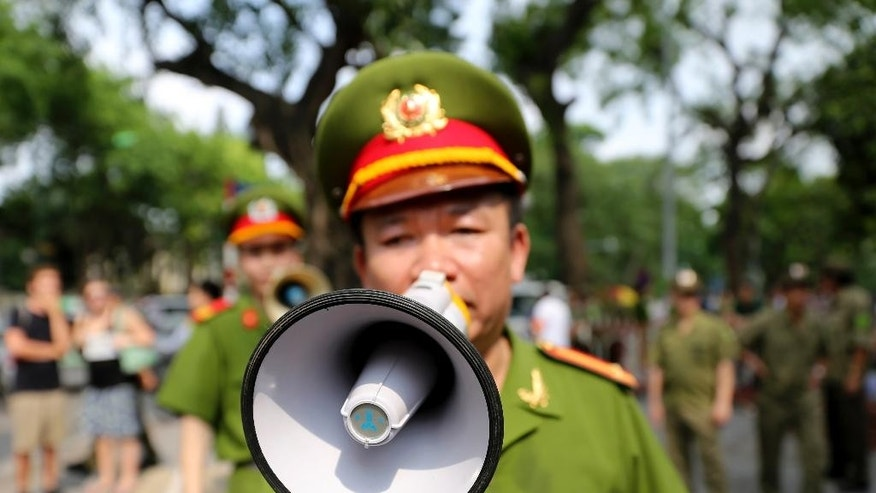 A Vietnamese police officer uses a speaker to order pedestrians including journalists to leave a closed area near the Chinese Embassy in Hanoi, Vietnam on Sunday, May 18, 2014. Vietnamese authorities forcibly broke up small protests against China in two cities on Sunday, after deadly anti-China rampages over a simmering territorial dispute risked damaging the economy and spooked a state used to keeping a tight grip on its people. In southern Ho Chi Minh City, police dragged away several demonstrators from a park in the city center. In Hanoi, authorities closed off streets and a park close to the Chinese Embassy and pushed journalists and protesters away.  (AP Photo/Na Son Nguyen)