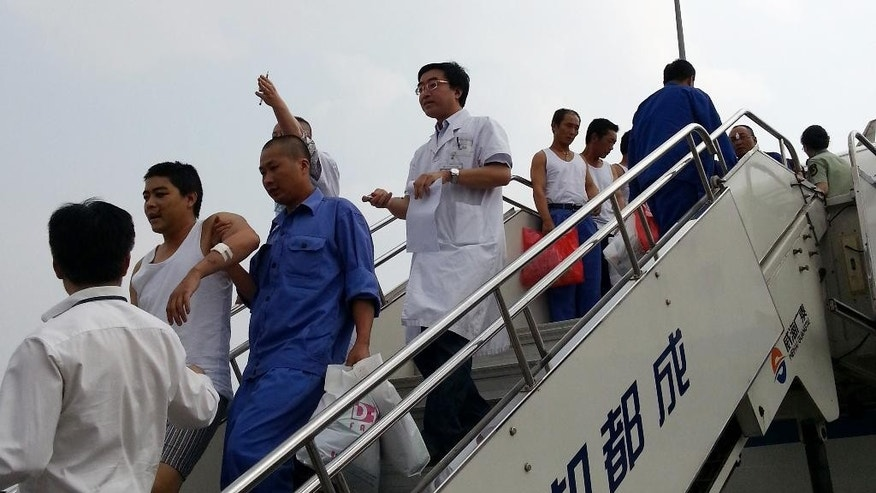 In this photo released by China's Xinhua News Agency,  over 290 Chinese nationals affected by Vietnam's anti-China riots arrive in Chengdu, the capital of southwest China's Sichuan Province, Sunday, May 18, 2014. China's Foreign Ministry said two charter flights carrying more than 290 Chinese employees from affected businesses arrived in Chengdu in southwest China on Sunday afternoon. They included more than 100 injured people. (AP Photo/Xinhua, Hai Mingwei) NO SALES