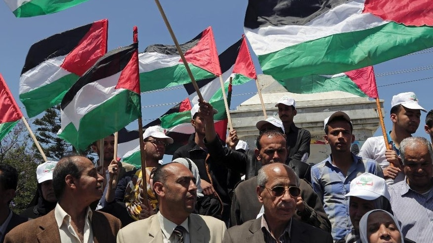 File - In this April 22, 2014 file photo, Palestinians wave their national flags during a rally to demand the end of Palestinian political divisions, at the main square of Gaza City. Propelled by crises, rivals Hamas and Fatah are moving toward forming a unity government by next week, in what appears to be their most promising attempt yet to end a seven-year rift that weakened the Palestinian case for statehood. (AP Photo/Adel Hana, File)