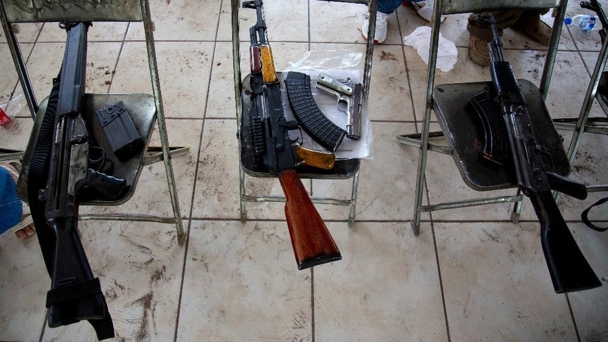 In this May 8, 2014 photo, weapons that belong to members of self-defense groups sit on chairs during a weapons registration operation in Apatzingan, Mexico. The self-defense members, identified by their white T-shirts, have registered thousands of weapons. But they've been allowed to keep them, even the large-caliber rifles that under Mexican law can only be used by the military. (AP Photo/Eduardo Verdugo)