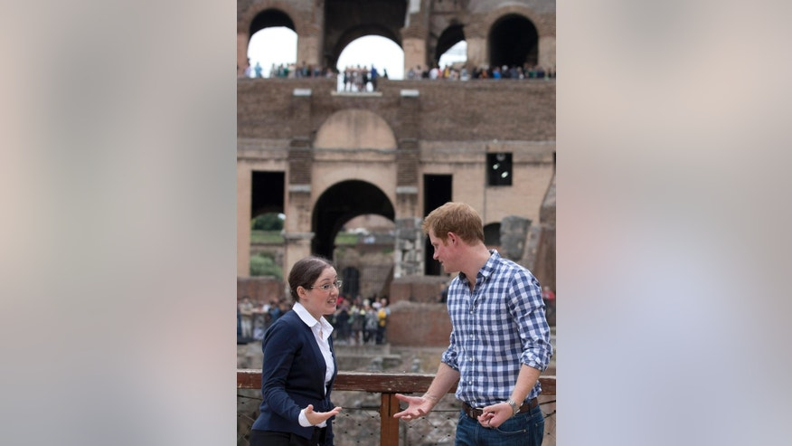 Britain's Prince Harry, right, listens to Italian guide Laura Ciglioni as he tours the Colosseum, in Rome, Monday, May 19, 2014. The Colosseum was the largest amphitheater of the Roman Empire and is today one of Rome's best know landmarks. Prince Harry is in Italy for a three-day visit to commemorate the 70th anniversary of the WWII's Monte Cassino battle. (AP Photo/Alessandra Tarantino, Pool)