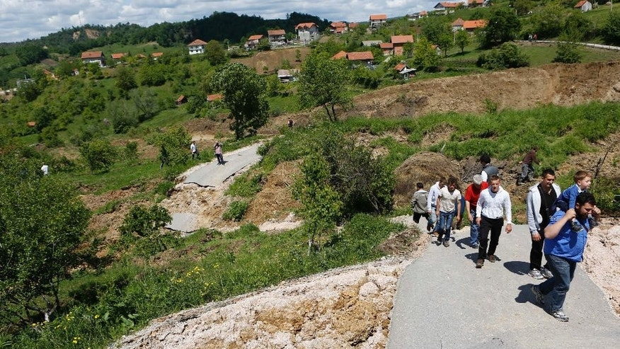 Bosnian people walk on a broken road after a landslide which swept away eight houses near Kalesija, Bosnia, 150 kms north of Sarajevo, Sunday May 18, 2014. Packed into buses, boats and helicopters, carrying nothing but a handful of belongings, tens of thousands fled their homes in Bosnia and Serbia, seeking to escape the worst flooding in a century. (AP Photo/Amel Emric)