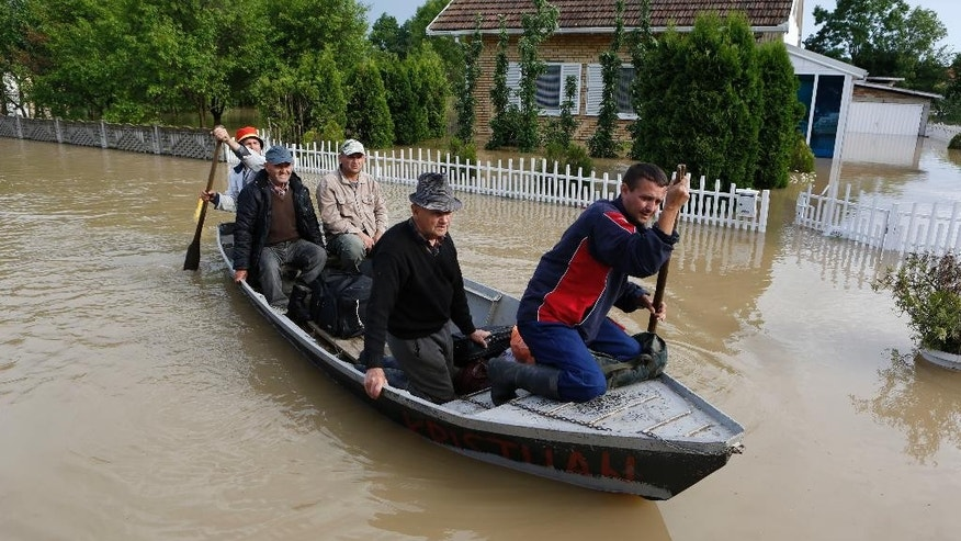 Bosnian people are rescued from their flooded houses by boat in the village of Vidovice near Orasje 200 kms north of Sarajevo, on Sunday May 18, 2014. Packed into buses, boats and helicopters, carrying nothing but a handful of belongings, tens of thousands fled their homes in Bosnia and Serbia, seeking to escape the worst flooding in a century. (AP Photo/Amel Emric)