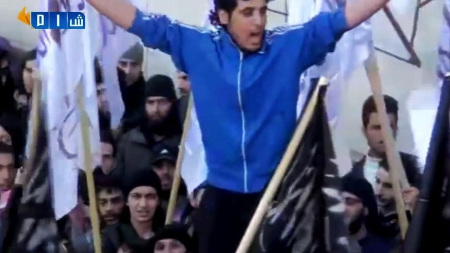 In this Feb. 13, 2014 image made from amateur video posted by Shaam News Network (SNN), an anti-Bashar Assad activist group, which has been verified and is consistent with other AP reporting, revolutionary goalkeeper Abdelbasit Sarout chants slogans during a demonstration in Homs, Syria. He began as a local hero on the soccer field, playing for the most popular team of his home city Homs and rising toward national stardom across Syria. But when the uprising against President Bashar Assad began, Sarout left all of it to lead peaceful protests, rallying thousands to demand Assad leave power. More than three years later, the former goalkeeper - now an armed fighter - has become a charismatic icon of the Syria's rebellion. (AP Photo/Shaam News Network via AP video)