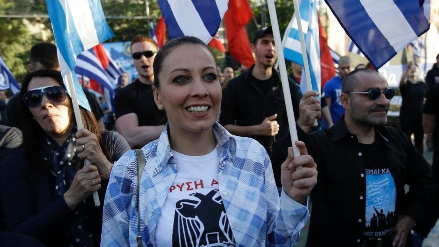 In this Wednesday, May 14, 2014 photo a supporter of far-right political party Golden Dawn wears a T-shirt reading ''Golden Dawn…We Are Coming'' during a rally in Athens. Struggling to form alliances, Europe's far-right is softening its image, as a wide variety of anti-establishment parties seek gains across a continent emerging from financial crisis. (AP Photo/Thanassis Stavrakis)