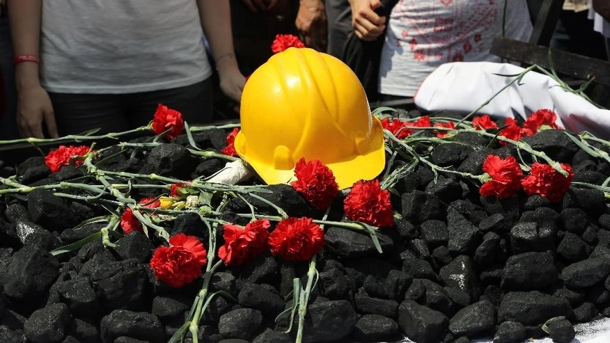 People place flowers on some coal and a hard hat as nearly 2,000 university students called on the government to resign as they marched to commemorate the beginning of the Turkish War of Independence started on May 19, 1919, in Ankara, Turkey, Monday, May 19, 2014. Government officials have promised to investigate and pledged that any mine officials found to be negligent would be punished. Still the disaster has provoked anger at a critical time for Prime Minister Recep Tayyip Erdogan, as he mulls running in August's presidential election. (AP Photo/Burhan Ozbilici)