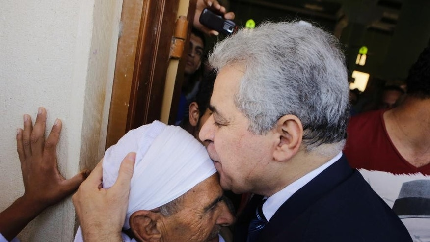 """FILE - In this Friday, May 16, 2014 file photo, presidential hopeful Hamdeen Sabahi kisses the head of an elderly relative following Friday prayers at Jerusalem mosque, in Baltim city, 212 kilometers (132 miles) north of Cairo, Egypt. The deep underdog in Egypt's presidential elections, candidate Sabahi is trying to rally youth behind him as the hope for the country's pro-democracy """"revolution"""" in his race against the former military chief, who some fear will bring back an autocratic rule. (AP Photo/Amr Nabil, File)"""
