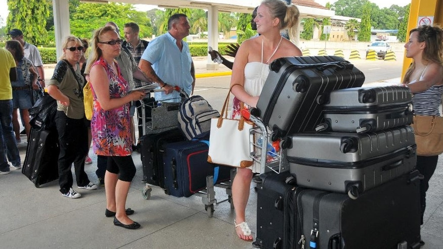 British tourists queue with their luggage to leave by charter flight from the international airport in Mombasa, Kenya Friday, May 16, 2014. Britain's government warned its citizens this week to avoid the coastal city of Mombasa and beach towns nearby, prompting a travel company to cut short the vacations of hundreds of British citizens and fly them home, while Kenya's National Disaster Operation Centre says that two explosions in Nairobi have killed at least four people Friday with one blast targeting a mini-van that Kenyans use for public transportation and a second blast went off in a market. (AP Photo)