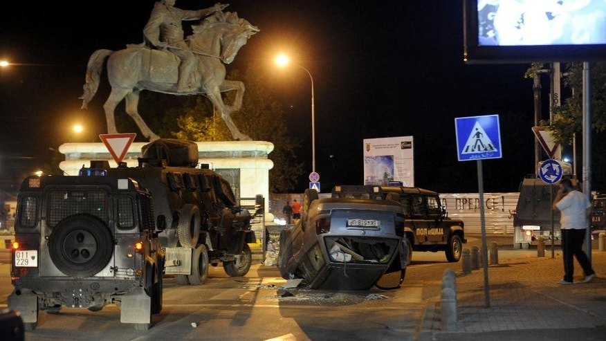 In this picture taken late Monday, May, 19, 2014, riot police vehicles pass by an overturned car on a street,  in Skopje, Macedonia. Police said Tuesday that 18 people were detained in a protest that turned violent late on Monday, after the murder of a 18-years old teenager in a western suburb of Macedonian capital Skopje. One man has been arrested in connection with the murder. (AP Photo/Boris Grdanoski)