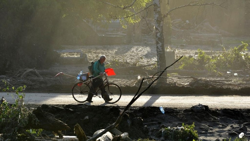 A man carrying a shovel pushes a bicycle after devastating floods in the town of Maglaj 140 kilometers North of Sarajevo, Bosnia-Herzegovina on Monday May 19, 2014. At least 35 people have died in Serbia and Bosnia in the five days of flooding caused by unprecedented torrential rain, laying waste to entire towns and villages and sending tens of thousands of people out of their homes, authorities said. (AP Photo/Sulejman Omerbasic)