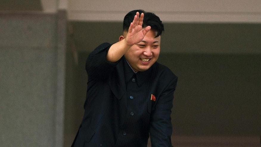 FILE - In this July 27, 2013 file photo, North Korean leader Kim Jong Un leans over a balcony and waves to Korean War veterans cheering below at the end of a mass military parade on Kim Il Sung Square in Pyongyang to mark the 60th anniversary of the Korean War armistice. When a South Korean ferry sank with hundreds trapped inside last month, the whole world knew about it. But in the North, there was utter silence about the collapse of a 23-story apartment building for five days, until state media issued a report and rare apology. North Korea is not a black hole for information. But with no Internet for most citizens, a slavish local press that operates as the government's propaganda wing and a security apparatus that severely curbs foreigners and citizens alike, if North Koreans get news about something, it is almost always because young leader Kim Jong Un wants them to get it. (AP Photo/David Guttenfelder, File)