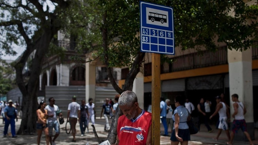 A man reads a copy of Cuba's state newspaper Granma while waiting for the bus in Havana, Cuba, Monday, May 19, 2014. Cuba's best-known blogger Yoani Sanchez and her husband Reinaldo Escobar say they will start publishing the country's first major independent general-interest newspaper in more than 50 years on Wednesday, in a move that will test both the government's openness to free expression and the dissident's ability to build a following inside her country. (AP Photo/Franklin Reyes)