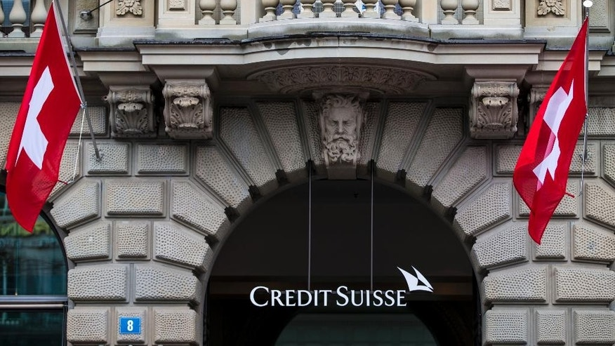 FILE - In this April 27, 2014 file picture  Swiss flags fly at the entrance of of Swiss bank Credit Suisse in Zurich, Switzerland.E uropean bank Credit Suisse AG pleaded guilty Monday May 19, 2014  to helping wealthy Americans avoid paying taxes through secret offshore accounts and agreed to pay about US $2.6 billion. The Justice Department said it was the largest penalty imposed in any criminal tax case. Credit Suisee is the largest bank to plead guilty in more than 20 years. (AP Photo/Keystone,Patrick B. Kraemer)