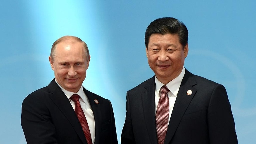 Russian President Vladimir Putin, left, shakes hands with Chinese President Xi Jinping before the opening ceremony at the Expo Center at the fourth Conference on Interaction and Confidence Building Measures in Asia (CICA) summit in Shanghai Wednesday, May 21, 2014.  China's president has called for creation of a new Asian structure for security cooperation based on a regional group that includes Russia and Iran and excludes the United States.  (AP Photo/Mark Ralston, Pool)