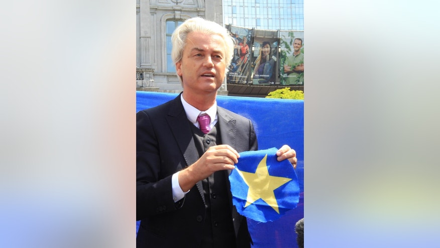 Dutch populist and euro-sceptic Geert Wilders shows a yellow star he cut out of the EU flag in front of the European Parliament in Brussels, Tuesday, May 20, 2014. Wilders is campaigning on a platform forbidding any further transfer of power to Europe, scrapping the Euro and control of immigration policy. (AP Photo/Yves Logghe)