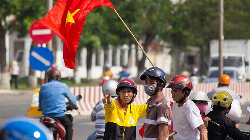 FILE - In this May 14, 2014 file photo, protesters stand on the corner of a street in Quan Doan 4, Binh Duong province, near Song Than 2 Industrial Park in Vietnam. China's planting of an oil platform in contested waters off Vietnam drew strident complaints from Hanoi, a messy standoff between ships and violent protests among Vietnamese _ but nothing to dislodge the rig and no broader pushback in the region.  (AP Photo/Jeff Nesmith, File)