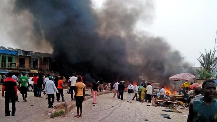 May 20, 2014: Smoke rises after a bomb blast at a bus terminal in Jos, Nigeria. Two explosions ripped through a bustling bus terminal and market frequented by thousands of people in Nigeria's central city of Jos on Tuesday afternoon. (AP Photo/Stefanos Foundation)