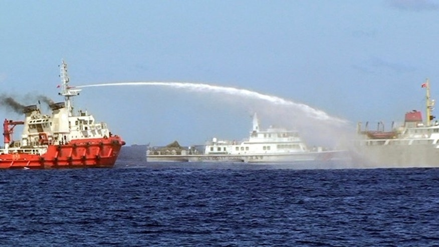 May 7, 2014: In this photo released by Vietnam Coast Guard, a Chinese ship, left, shoots water cannon at a Vietnamese vessel, right, while a Chinese Coast Guard ship, center, sails alongside in the South China Sea, off Vietnam's coast. Chinese ships were ramming and spraying water cannons at Vietnamese vessels trying to stop Beijing from setting up an oil rig in the South China Sea, according to Vietnamese officials and video evidence.