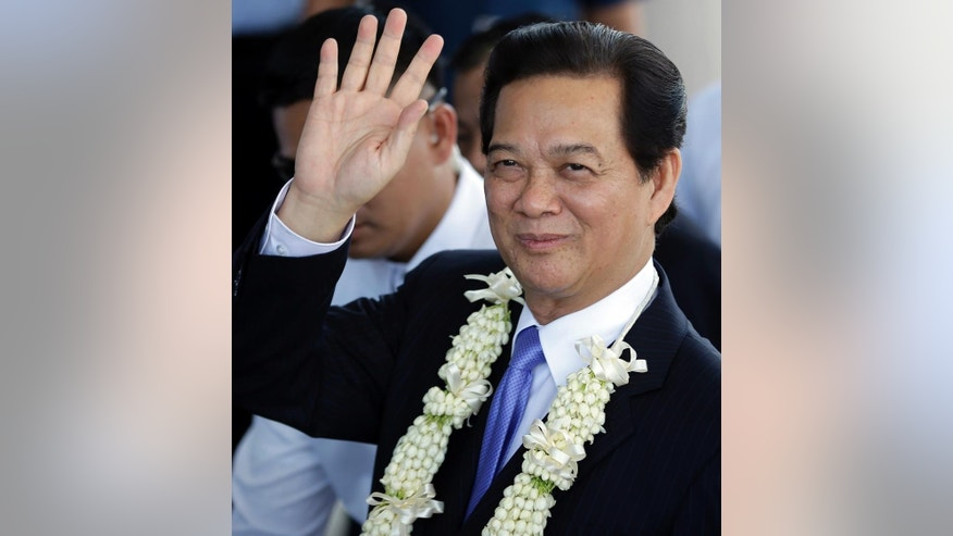 Vietnamese Prime Minister Nguyen Tan Dung waves to media shortly upon arrival at the Manila International Airport in Manila, Philippines Wednesday, May 21, 2014.  Prime Minister Dung is here for the World Economic Forum in East Asia and for talks with Philippine President Benigno Aquino III that will focus on toughening cooperation as their countries wrangle with China in tense territorial standoffs in the South China Sea. (AP Photo/Bullit Marquez)