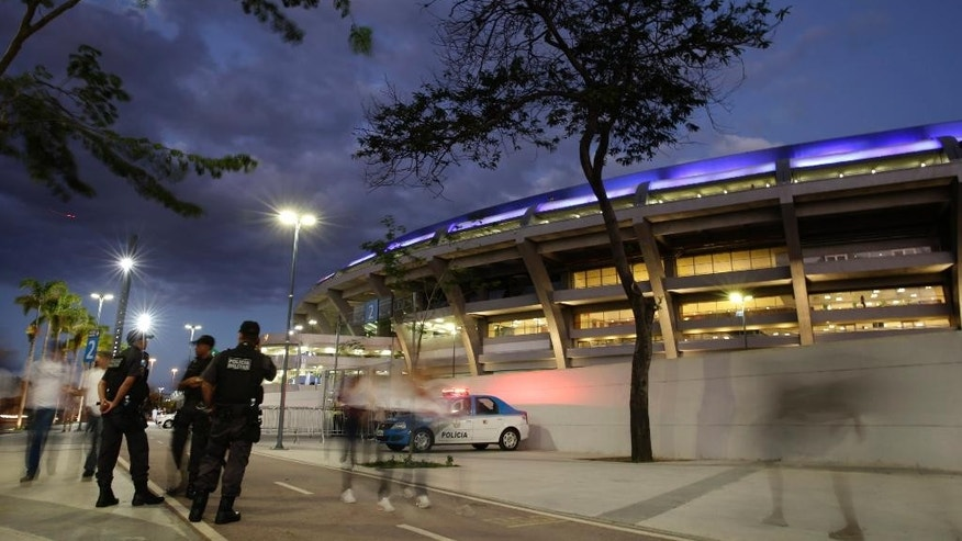 In this Sunday, May 11, 2014 photo, police stand outside the Maracana stadium, before a Brazilian league soccer match between Fluminense and Flamengo, in Rio de Janeiro, Brazil. Muggings on public transportation, public beaches and in popular tourist areas are on the rise in Rio de Janeiro, eroding the strides the city had made in security in recent years as it geared up to host six World Cup matches and the 2016 Olympic. (AP Photo/Hassan Ammar)