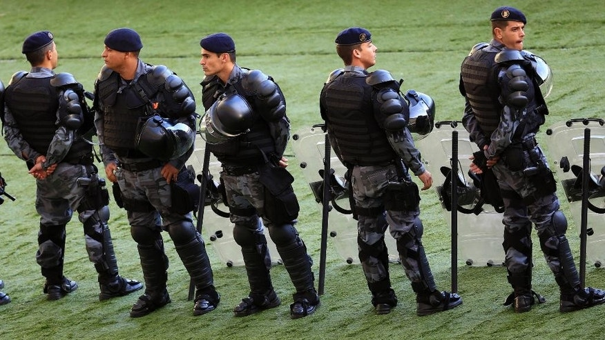In this Sunday, May 11, 2014 photo, policemen stand guard inside the Maracana stadium, during the Brazilian league soccer match between Fluminense and Flamengo, in Rio de Janeiro, Brazil. Muggings on public transportation, public beaches and in popular tourist areas are on the rise in Rio de Janeiro, eroding the strides the city had made in security in recent years as it geared up to host six World Cup matches and the 2016 Olympic. (AP Photo/Hassan Ammar)
