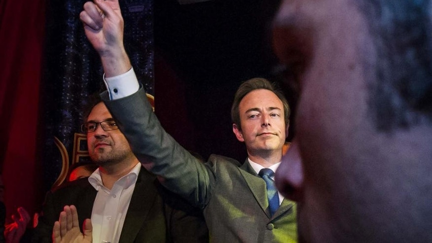 FILE In this Oct. 14, 2012 file photo, leader of the N-VA party Bart De Wever makes a victory sign, as he talks at the N-VA election meeting, after they won the municipal elections in Antwerp, Belgium. Walk through Belgium and feel that giddy sense of unity, the national football team is going to the World Cup again. Follow the election campaign though, and the division between Dutch- and French-speakers seems even worse than four years ago when it took a record 541 days to form a government uniting the bickering sides. (AP Photo/Geert Vanden Wijngaert, file)