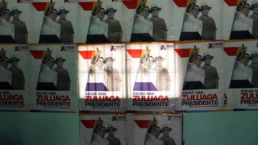 FILE - In this May 17, 2014 file photo, campaign posters promoting Democratic Center Party presidential candidate Oscar Ivan Zuluaga, pictured with former President Alvaro Uribe, right, blanket a wall in Villeta, Colombia. Accusations of bribes from drug traffickers, spying and email hacking have turned Colombia's presidential election into an ugly slugfest that has further polarized a country trying to emerge from its violent past. Much of the blame for the dirty campaigning falls on two former allies whose public feuding has divided Colombia the past four years: President Juan Manuel Santos and his still powerful predecessor, Alvaro Uribe. (AP Photo/Fernando Vergara)