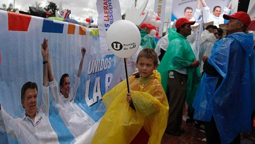 FILE - In this May 17, 2014 file photo, a boy holds a balloon during a campaign event for Colombia's President and Social Party of National Unity presidential candidate, Juan Manuel Santos, in Bogota, Colombia. Accusations of bribes from drug traffickers, spying and email hacking have turned Colombia's presidential election into an ugly slugfest that has further polarized a country trying to emerge from its violent past. (AP Photo/Javier Galeano, File)