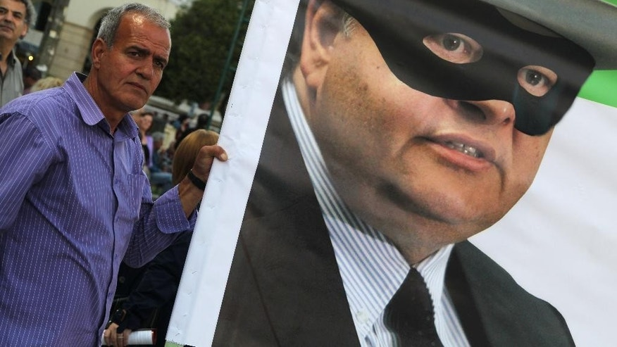 A small bond-holder holds a banner with a picture of the leader of Greece's Socialist party, Evangelos Venizelos wearing a mask during a speech by Greek left-wing opposition leader Alexis Tsipras, in the northern Greek city of Thessaloniki on Wednesday, May 21, 2014. Around 400 million Europeans voters in 28 countries on Thursday begin choosing the next European Parliament and helping determine the EU's future leaders and course. Greece's rickety coalition government faces its second electoral test in local, regional and European parliamentary elections on Sunday which the left-wing opposition has billed as a referendum on the country's bailout. (AP Photo/Nikolas Giakoumidis)