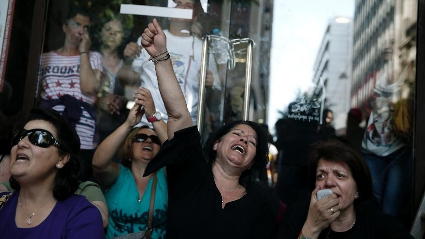 Laid-off Greek Finance Ministry cleaning staff  shout slogans as they block the entrance of a Finance Ministry building in central Athens, on Thursday, May 22, 2014. Dozens took part in the protest, demanding that the government respects a recent court decision to reinstate them in their jobs. The May 12 ruling found that 397 cleaners who made the complaint were wrongfully suspended from their jobs eight months ago, as part of a state sector staff reduction program. (AP Photo/Petros Giannakouris)