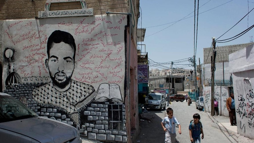 In this photo taken Tuesday, May 20, 2014, two Palestinian school children walk past a mural depicting late Palestinian activist Ahmed Mosleh, who was killed during an Israeli army operation in 2006, with his name in Arabic and the names of other killed Palestinians, in an alley of the Dheisheh Palestinian refugee camp, in the West Bank city of Bethlehem. Pope Francis will spend less than half an hour in this Palestinian refugee camp during a jam-packed Holy Land tour this weekend, but residents hope even a brief visit will shine a light on what they say is their forgotten plight. Some 190,000 of the West Bank's 2.4 million Palestinians live in refugee camps and face tougher conditions _ including higher unemployment and overcrowding _ than their neighbors in towns and villages. (AP Photo/Nasser Nasser)