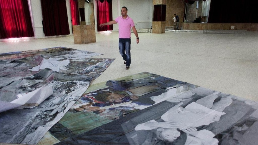 In this photo taken Tuesday, May 20, 2014, a Palestinian worker spreads large posters on the ground to prepare them for decoration of the main hall that will receive Pope Francis during his upcoming visit to the Holly Land this weekend, at the Phoenix center in the Dheisheh Palestinian refugee camp, in the West Bank city of Bethlehem. Pope Francis will spend less than half an hour in this Palestinian refugee camp during a jam-packed Holy Land tour this weekend, but residents hope even a brief visit will shine a light on what they say is their forgotten plight. Some 190,000 of the West Bank's 2.4 million Palestinians live in refugee camps and face tougher conditions _ including higher unemployment and overcrowding _ than their neighbors in towns and villages. (AP Photo/Nasser Nasser)
