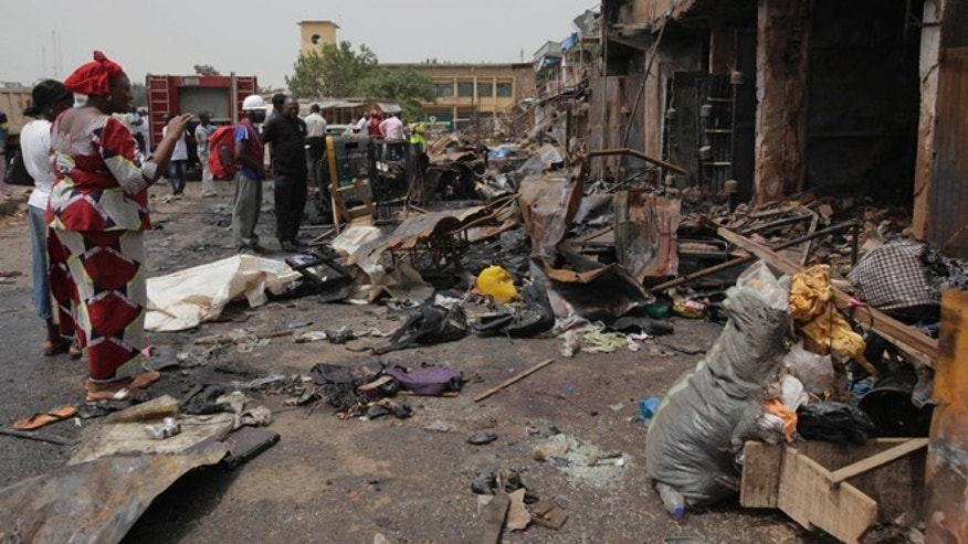 May 21, 2014: Onlookers gather at the site of one of Tuesday's car bombings in Jos, Nigeria. (AP)