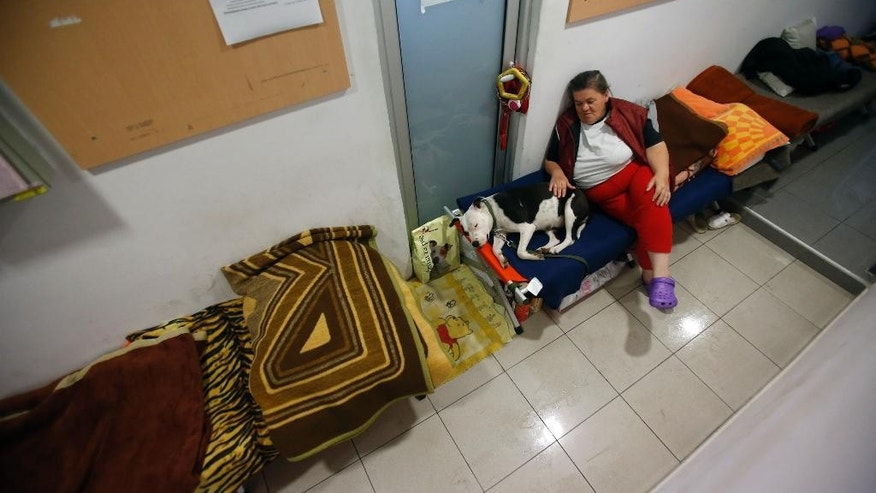 A woman from the flood-hit town of Obrenovac and her dog sit on make-shift beds in a shelter in Belgrade, Serbia, Thursday, May 22, 2014. Serbia, Bosnia and Croatia have been hit by the worst flooding in more than 100 years, forcing half a million people out of their homes and leading to more than three dozen deaths. (AP Photo/Darko Vojinovic)