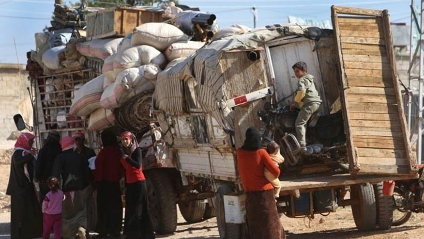 FILE -- In this Tuesday April 22, 2014 file photo, Syrian refugees who fled from the Syrian town of Rankous, stand next to trucks which carry their belongings, in Tfail village, at the Lebanese-Syrian border, eastern Lebanon. (AP Photo/Hussein Malla, File)