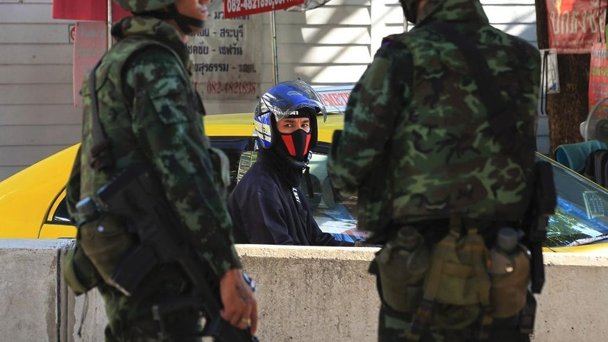 Thai soldiers guard on a street in Bangkok, Thailand, Thursday, May 22, 2014. Thailand's army chief Gen. Prayuth Chan-Ocha assumed the role of mediator Wednesday by summoning the country's key political rivals for face-to-face talks one day after imposing martial law. The meeting ended without any resolution, however, underscoring the profound challenge the army faces in trying to end the country's crisis. (AP Photo/Sakchai Lalit)