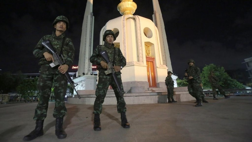Thai soldiers stand guard in front of the Democracy Monument after the coup Thursday, May 22, 2014 in Bangkok, Thailand. Thailand's military seized power Thursday in a bloodless coup, dissolving the government, suspending the constitution and dispersing groups of protesters from both sides of the country's political divide who had gathered in Bangkok and raised fears of a violent showdown. (AP Photo/Sakchai Lalit)