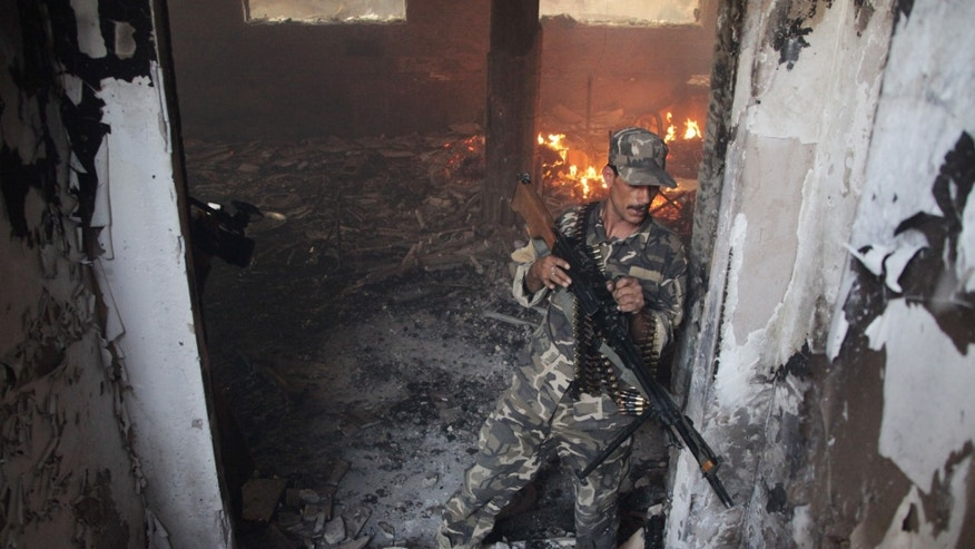 May 23, 2014 - Afghan soldier takes position at the site of a clash between insurgents and security forces at the Indian Consulate in Herat, Afghanistan.